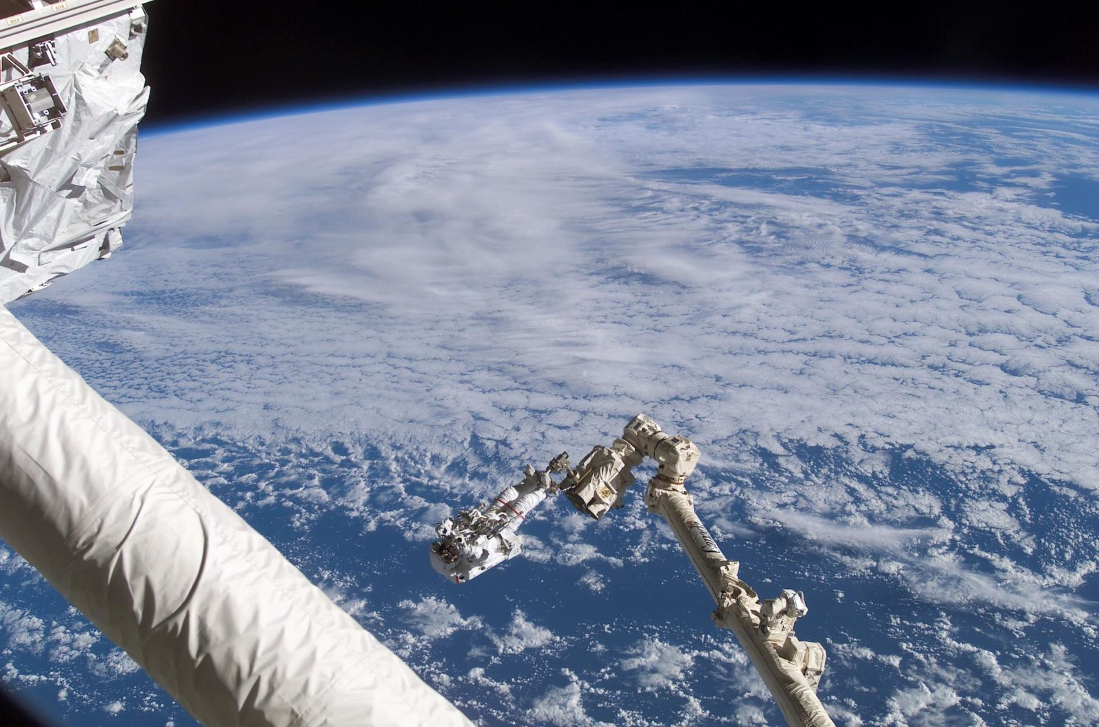 Chang-Diaz on the Canadarm2 SSRMS backdropped against Earth limb during  STS-111 UF-2 EVA 1