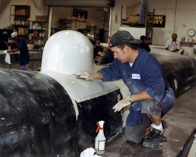Technician Shawn Warren carefully smoothes out the composite skin of an instrument fairing<br>atop the upper fuselage of the Altair unmanned aerial vehicle (UAV) at General Atomics Aeronautical Systems, Inc., facility at Adelanto, Calif. EC02-0188-3