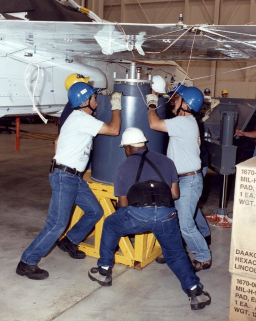 NASA Dryden technicians (Dave Dennis, Freddy Green and Jeff Doughty) position a support cylinder under the right wing of the Active Aeroelastic Wing F/A-18 test aircraft prior to ground vibration tests. EC02-0203-14
