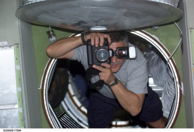 Yurchikhin uses a still photo camera while floating in the SM during Expedition Five on the ISS