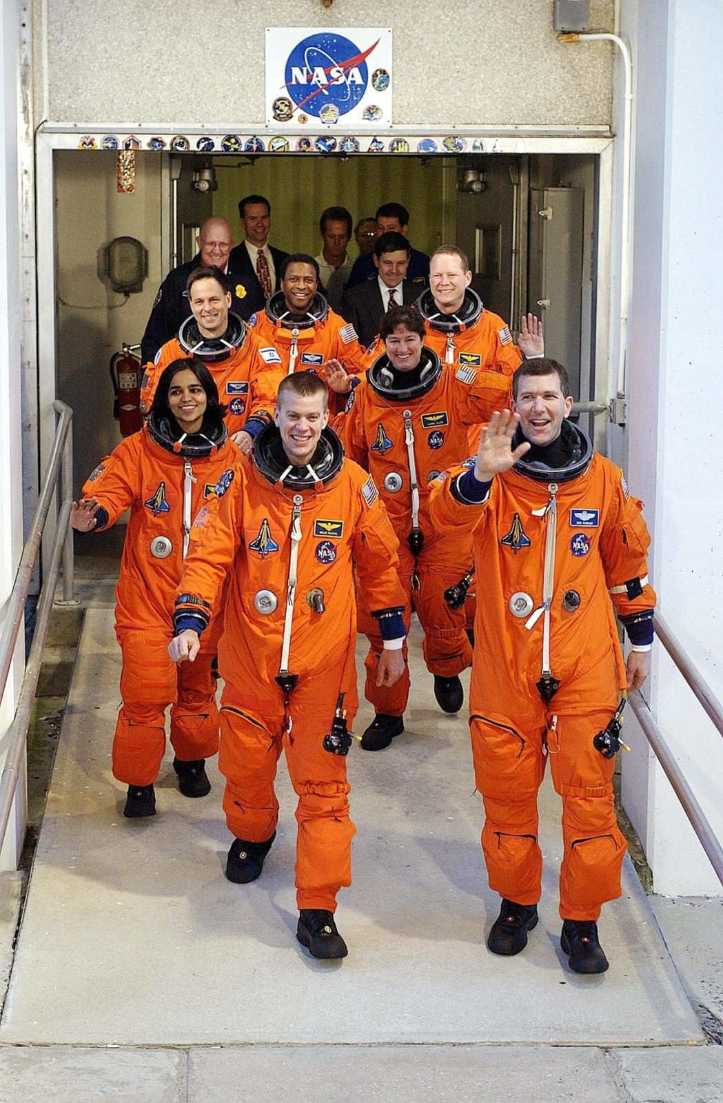 """KENNEDY SPACE CENTER, FLA. - .  The STS-107 crew, waving to onlookers, exits the Operations and Checkout Building on their way to Launch Pad 39A for liftoff.  Leading the way are Pilot William """"Willie"""" McCool (left) and Commander Rick Husband (right).  Following in the second row are Mission Specialists Kalpana Chawla (left) and Laurel Clark; in the rear are Payload Specialist Ilan Ramon, Payload Commander Michael Anderson and Mission Specialist David Brown.  Ramon is the first astronaut from Israel to fly on a Shuttle. The 16-day mission is devoted to research and will include more than 80 experiments that will study Earth and space science, advanced technology development, and astronaut health and safety. The payload on Space Shuttle Columbia includes FREESTAR (Fast Reaction Experiments Enabling Science, Technology, Applications and Research) and the SHI Research Double Module (SHI/RDM), known as SPACEHAB.  Experiments on the module range from material sciences to life sciences.  Liftoff is scheduled for 10:39 a.m. EST.  [Photo courtesy of Scott Andrews] KSC-03pd0109"""