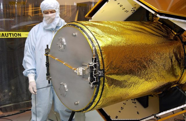 KENNEDY SPACE CENTER, FLA. -- In the Multi-Payload Processing Facility, workers check the deployment of the cover of the telescope on the GALEX satellite. The Galaxy Evolution Explorer (GALEX) is an orbiting space telescope that will observe galaxies in ultraviolet light across 10 billion years of cosmic history. Led by the California Institute of Technology, GALEX will conduct several first-of-a-kind sky surveys, including an extra-galactic (beyond our galaxy) ultraviolet all-sky survey. During its 29-month mission GALEX will produce the first comprehensive map of a Universe of galaxies under construction, bringing more understanding of how galaxies like the Milky Way were formed.  GALEX is due to be launched from Cape Canaveral Air Force Station March 25 via a Pegasus rocket. KSC-03pd0484