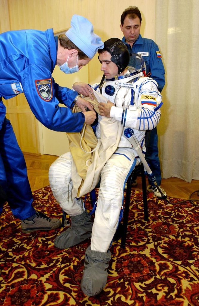 Baikonur Cosmodrome, Kazakhstan -- Cosmonaut Yuri I. Malenchenko, Expedition Seven commander, dons his Russian Sokol suit for the leak check and Soyuz inspection, seat liner check. Veteran Russian cosmonaut Yuri Malenchenko and veteran NASA astronaut Ed Lu have been named as the primary crew for the planned April 26, 2003, launch of a Russian Soyuz TMA-2 spacecraft to the International Space Station. Malenchenko and Lu will be called the Expedition 7 crew. Russian cosmonaut Alexander Kaleri and NASA astronaut Michael Foale are the backup crewmembers to Malenchenko and Lu.  Expedition 6 Commander Ken Bowersox, Flight Engineer Nikolai Budarin and NASA Space Station Science Officer Don Pettit will return to Earth aboard the Soyuz TMA-1 craft in May 2003. The three Expedition 6 crewmembers were launched on Nov. 23, 2002. They have been aboard the Station since November 25. They were originally scheduled to return in March aboard the Space Shuttle Atlantis during the STS-114 mission.  Malenchenko and Lu will continue to operate the science payloads already on board, as well as maintaining the Station.  Photo Credit: NASA/Bill Ingalls KSC-03pd1257