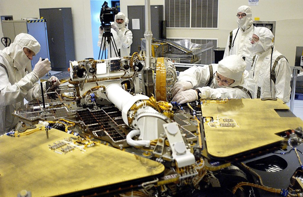 KENNEDY SPACE CENTER, FLA. -- In the Payload Hazardous Servicing Facility, technicians remove one of the circuit boards on the Mars Exploration Rover 2 (MER-2).  To gain access to the spacecraft, its lander petals were reopened and its solar panels deployed.  A concern arose during prelaunch testing regarding how the spacecraft interprets signals sent from its main computer to peripherals in the cruise stage, lander and small deep space transponder.  The MER Mission consists of two identical rovers set to launch in June 2003. The problem will be fixed on both rovers. KSC-03pd1140