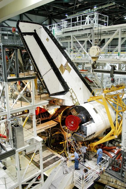 KENNEDY SPACE CENTER, FLA. -  Workers in the Orbiter Processing Facility prepare to remove one of two orbital maneuvering system (OMS) pods from Endeavour.  The OMS pods are attached to the upper aft fuselage left and right sides.  Fabricated primarily of graphite epoxy composite and aluminum, each pod is 21.8 feet long and 11.37 feet wide at its aft end and 8.41 feet wide at its forward end, with a surface area of approximately 435 square feet. Each pod houses the Reaction Control System propulsion components used for inflight maneuvering and is attached to the aft fuselage with 11 bolts.  OMS pods are removed during Orbiter Major Modifications. Once removed, the OMS pods undergo in-depth structural inspections, system checks and the thrusters are changed out.