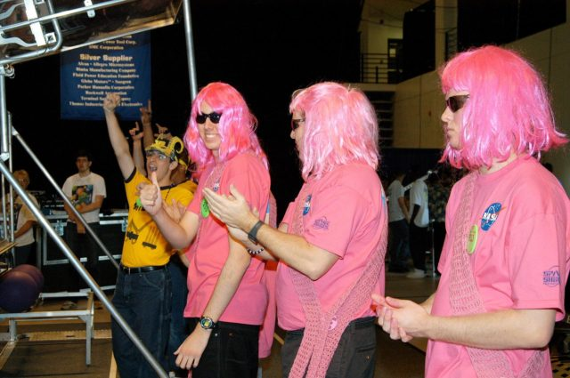 """KENNEDY SPACE CENTER, FLA. -  During the 2004 Florida Regional FIRST competition in the University of Central Florida Arena, the KSC-sponsored """"Pink"""" team applauds a win by the yellow-clad Central Florida team. The event hosted 41 teams from Canada, Brazil, Great Britain and the United States.  Among observers at the annual event were Center Director Jim Kennedy and Florida Gov. Jeb Bush, who spoke at the event luncheon.  FIRST is a nonprofit organization, For Inspiration and Recognition of Science and Technology, that sponsors the event pitting gladiator robots against each other in an athletic-style competition. The FIRST robotics competition is designed to provide students with a hands-on, inside look at engineering and other professional careers, pairing high school students with engineer mentors and corporations. KSC-04pd0476"""