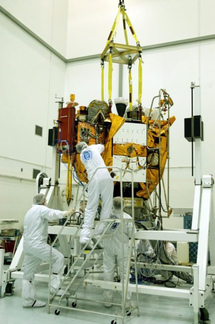 KENNEDY SPACE CENTER, FLA. -- Astrotech Space Operations facilities near KSC, workers remove protective covers from the Mercury Surface, Space Environment, Geochemistry and Ranging (MESSENGER) spacecraft now resting on the turnover fixture.  Workers will perform the propulsion system phasing test - firing gas through the thrusters in order to verify that the right thrusters fire when expected - as part of prelaunch testing at the site.  Launch is scheduled for May 11 from Pad 17-B, Cape Canaveral Air Force Station. The spacecraft will fly past Venus three times and Mercury twice before starting a year-long orbital study of Mercury in July 2009. KSC-04pd0672