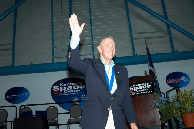 """KENNEDY SPACE CENTER, FLA. -- Former astronaut Joe Engle acknowledges the applause as he is introduced as a previous inductee into the U.S. Astronaut Hall of Fame.  He and other  Hall of Fame members were present for the induction of five new space program heroes into the U.S. Astronaut Hall of Fame: Richard O. Covey, commander of the Hubble Space Telescope repair mission; Norman E. Thagard, the first American to occupy Russia's Mir space station; the late Francis R. """"Dick"""" Scobee, commander of the ill-fated 1986 Challenger mission; Kathryn D. Sullivan, the first American woman to walk in space; and Frederick D. Gregory, the first African-American to command a space mission and the current NASA deputy administrator. Engle made 16 flights in the X-15 rocket plane before he became a NASA astronaut and flew two Space Shuttle missions. In 1981, he commanded the second flight of Columbia, the first manned spacecraft to be reflown in space, and in 1985 he commanded a five-man crew on the 20th shuttle flight, a satellite-deploy and repair mission.  The induction ceremony was held at the Apollo/Saturn V Center at KSC.  The U.S. Astronaut Hall of Fame opened in 1990 to provide a place where space travelers could be remembered for their participation and accomplishments in the U.S. space program. The five inductees join 52 previously honored astronauts from the ranks of the Gemini, Apollo, Skylab, Apollo-Soyuz, and Space Shuttle programs. KSC-04pd1018"""
