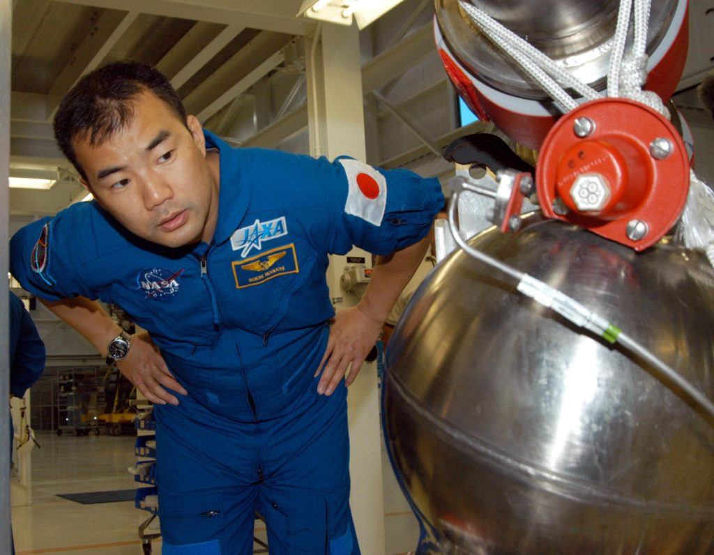 KENNEDY SPACE CENTER, FLA. -- STS-114 Mission Specialist Soichi Noguchi looks closely at low pressure oxidizer duct in the Space Shuttle Main Engine Shop at KSC.  He and other crew members are touring several areas on the Center.  The STS-114 mission is Logistics Flight 1, which is scheduled to deliver supplies and equipment plus the external stowage platform to the International Space Station. KSC-04pd1056