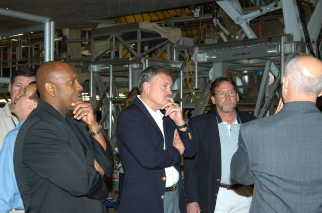 KENNEDY SPACE CENTER, FLA. -- Adm. Craig E. Steidle (center), NASA's associate administrator, Office of Exploration Systems, listens to Conrad Nagel, chief of the Shuttle Project Office (right), during a tour of the Orbiter Processing Facility on a visit to KSC.  They are standing under the orbiter Discovery.  The Office of Exploration Systems was established to set priorities and direct the identification, development and validation of exploration systems and related technologies to support the future space vision for America.  Steidle's visit included a tour of KSC to review the facilities and capabilities to be used to support the vision. KSC-04pd1140