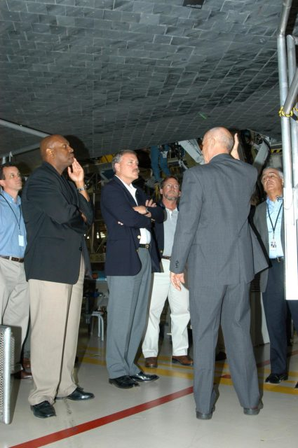 KENNEDY SPACE CENTER, FLA. -- Adm. Craig E. Steidle (center), NASA's associate administrator, Office of Exploration Systems, listens to Conrad Nagel, chief of the Shuttle Project Office (right), during a tour of the Orbiter Processing Facility on a visit to KSC.  They are standing under the orbiter Discovery.  The Office of Exploration Systems was established to set priorities and direct the identification, development and validation of exploration systems and related technologies to support the future space vision for America.  Steidle's visit included a tour of KSC to review the facilities and capabilities to be used to support the vision. KSC-04pd1141