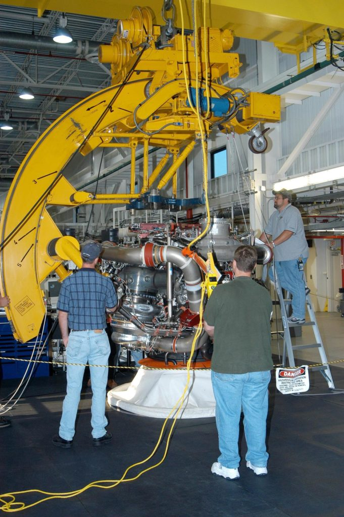 KENNEDY SPACE CENTER, FLA. - In the Space Shuttle Main Engine (SSME) Processing Facility, Boeing-Rocketdyne technicians prepare to move SSME 2058, the first SSME fully assembled at KSC. Move conductor Bob Brackett (on ladder) supervises the placement of a sling around the engine with the assistance of crane operator Joe Ferrante (center) and a technician. The engine will be lifted from its vertical work stand into a horizontal position in preparation for shipment to NASA's Stennis Space Center in Mississippi to undergo a hot fire acceptance test. It is the first of five engines to be fully assembled on site to reach the desired number of 15 engines ready for launch at any given time in the Space Shuttle program. A Space Shuttle has three reusable main engines. Each is 14 feet long, weighs about 7,800 pounds, is seven-and-a-half feet in diameter at the end of its nozzle, and generates almost 400,000 pounds of thrust. Historically, SSMEs were assembled in Canoga Park, Calif., with post-flight inspections performed at KSC.  Both functions were consolidated in February 2002. The Rocketdyne Propulsion and Power division of The Boeing Co. manufactures the engines for NASA. KSC-04pd1641
