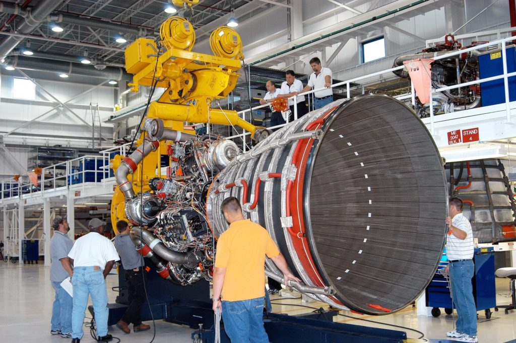 KENNEDY SPACE CENTER, FLA. - In the Space Shuttle Main Engine (SSME) Processing Facility, Boeing-Rocketdyne move conductor Bob Brackett (left) oversees the work of technicians on his team as they secure SSME 2058, the first SSME fully assembled at KSC, onto an engine stand. The engine is being placed into a horizontal position in preparation for shipment to NASA's Stennis Space Center in Mississippi to undergo a hot fire acceptance test. It is the first of five engines to be fully assembled on site to reach the desired number of 15 engines ready for launch at any given time in the Space Shuttle program. A Space Shuttle has three reusable main engines. Each is 14 feet long, weighs about 7,800 pounds, is seven-and-a-half feet in diameter at the end of its nozzle, and generates almost 400,000 pounds of thrust. Historically, SSMEs were assembled in Canoga Park, Calif., with post-flight inspections performed at KSC.  Both functions were consolidated in February 2002. The Rocketdyne Propulsion and Power division of The Boeing Co. manufactures the engines for NASA. KSC-04pd1649