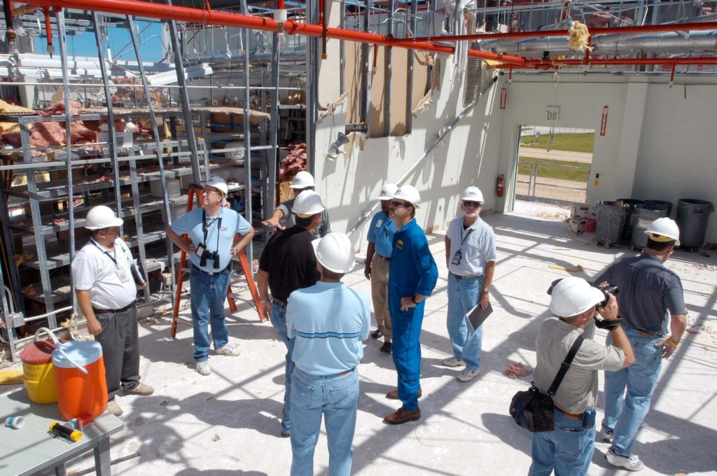 KENNEDY SPACE CENTER, FLA. -  Members of a hurricane assessment team from Johnson Space Center and Marshall Space Flight Center observe the damage to the roof of the Thermal Protection System (TPS) Facility at KSC after Hurricane Frances hit the east coast of Central Florida and Kennedy Space Center.   Near the center is astronaut Scott Altmann, a member of the team.  The facility, which creates the TPS tiles, blankets and all the internal thermal control systems for the Space Shuttles, is almost totally unserviceable at this time after losing approximately 35 percent of its roof.  Equipment and materials that survived the storm have been relocated to the RLV hangar near the KSC Shuttle Landing Facility. KSC-04pd1772