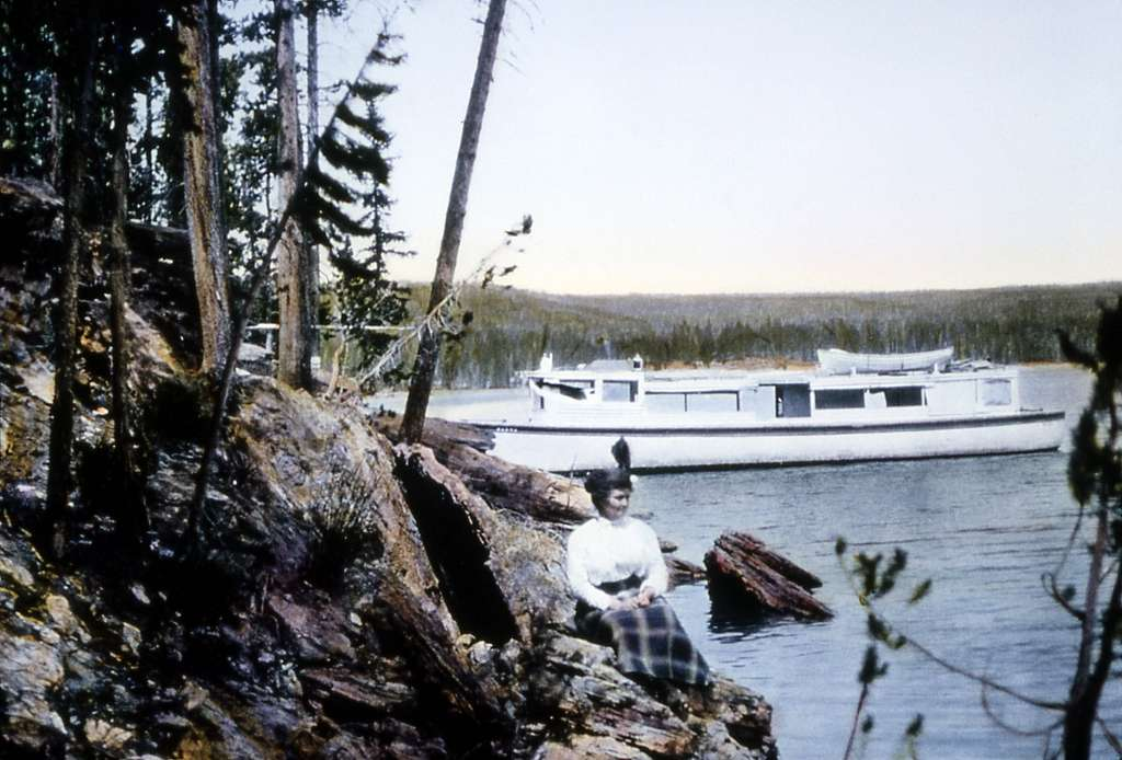 Visitor sitting on the shore of Yellowstone Lake with boat in water; JP Clum Lantern slide; No date