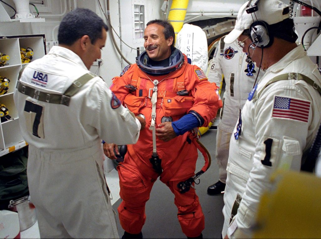 KENNEDY SPACE CENTER, FLA. -  STS-114 Mission Specialist Charles Camarda is helped by the Closeout Crew with his launch and entry suit before entering Space Shuttle Discovery.  This is Camarda's first Shuttle flight.  The Return to Flight mission to the International Space Station carries the External Stowage Platform-2, equipped with spare part assemblies, and a replacement Control Moment Gyroscope contained in the Lightweight Multi-Purpose Experiment Support Structure and Multi-Purpose Logistics Module Raffaello, housing 15 tons of hardware and supplies that will be transferred to the Station after the Shuttle docks to the complex .  On this mission, the crew will perform inspections on-orbit for the first time of all of the Reinforced Carbon-Carbon (RCC) panels on the leading edge of the wings and the Thermal Protection System tiles using the new Canadian-built Orbiter Boom Sensor System and the data from 176 impact and temperature sensors. Mission Specialists will also practice repair techniques on RCC and tile samples during a spacewalk in the payload bay. KSC-05pp1794