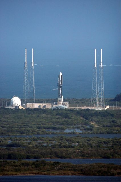KENNEDY SPACE CENTER, FLA. -  The Atlas V rocket with the New Horizons spacecraft on top sits waiting on the launch pad at Complex 41 at Cape Canaveral Air Force Station in Florida.  The view is from the top of the Vehicle Assembly Building at NASA Kennedy Space Center.  Surrounding the launch vehicle are four lightning masts.  The launch on this date was scrubbed due to high surface winds in the area and has been rescheduled for 1:16 p.m. EST Jan. 18. The compact, 1,050-pound piano-sized probe will get a boost from a kick-stage solid propellant motor for its journey to Pluto. New Horizons will be the fastest spacecraft ever launched, reaching lunar orbit distance in just nine hours and passing Jupiter 13 months later.  The launch at this time allows New Horizons to fly past Jupiter in early 2007 and use the planet's gravity as a slingshot toward Pluto. The Jupiter flyby trims the trip to Pluto by as many as five years and provides opportunities to test the spacecraft's instruments and flyby capabilities on the Jupiter system. New Horizons could reach the Pluto system as early as mid-2015, conducting a five-month-long study possible only from the close-up vantage of a spacecraft.  Photo credit: NASA/Kim Shiflett KSC-06pd0077