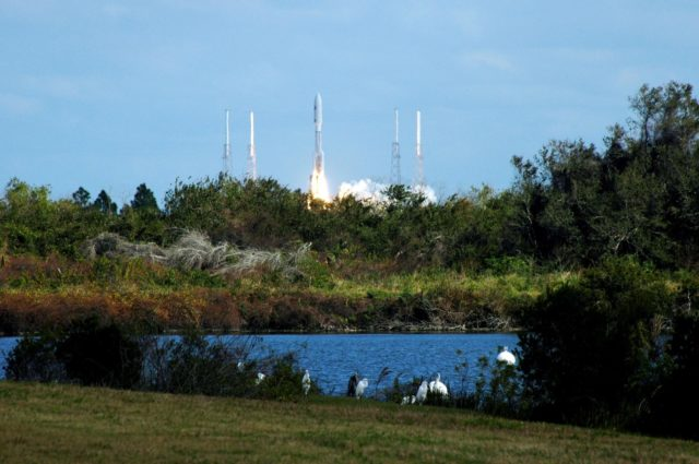 KENNEDY SPACE CENTER, FLA.  -- Great white egrets and a great blue heron in the foreground seem to stand watch as NASA's New Horizons spacecraft leaps off the pad on time at 2 p.m. EST aboard an Atlas V rocket from Complex 41 on Cape Canaveral Air Force Station in Florida.  This was the third launch attempt in as many days after scrubs due to weather concerns.   The compact, 1,050-pound piano-sized probe will get a boost from a kick-stage solid propellant motor for its journey to Pluto. New Horizons will be the fastest spacecraft ever launched, reaching lunar orbit distance in just nine hours and passing Jupiter 13 months later. The New Horizons science payload, developed under direction of Southwest Research Institute, includes imaging infrared and ultraviolet spectrometers, a multi-color camera, a long-range telescopic camera, two particle spectrometers, a space-dust detector and a radio science experiment. The dust counter was designed and built by students at the University of Colorado, Boulder. The launch at this time allows New Horizons to fly past Jupiter in early 2007 and use the planet's gravity as a slingshot toward Pluto. The Jupiter flyby trims the trip to Pluto by as many as five years and provides opportunities to test the spacecraft's instruments and flyby capabilities on the Jupiter system. New Horizons could reach the Pluto system as early as mid-2015, conducting a five-month-long study possible only from the close-up vantage of a spacecraft.  Photo credit: NASA/Ken Thornsley KSC-06pd0080