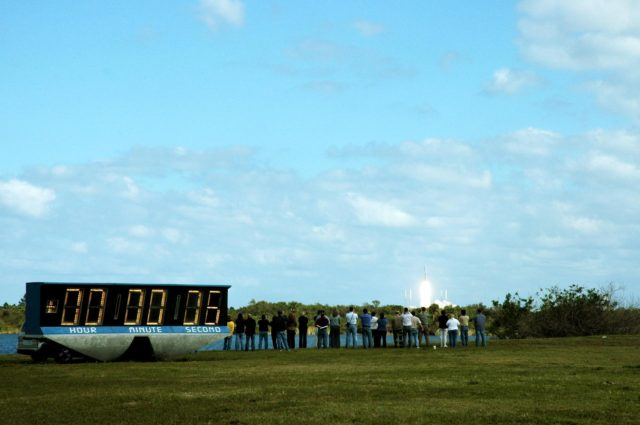 KENNEDY SPACE CENTER, FLA.  —  Spectators and photographers enjoy the view as the NASA New Horizons spacecraft clears the horizon six seconds into the launch (as seen on the countdown clock at left). The spacecraft lifted off on time at 2 p.m. EST aboard an Atlas V rocket from Complex 41 on Cape Canaveral Air Force Station in Florida.  This was the third launch attempt in as many days after scrubs due to weather concerns.   The compact, 1,050-pound piano-sized probe will get a boost from a kick-stage solid propellant motor for its journey to Pluto. New Horizons will be the fastest spacecraft ever launched, reaching lunar orbit distance in just nine hours and passing Jupiter 13 months later. The New Horizons science payload, developed under direction of Southwest Research Institute, includes imaging infrared and ultraviolet spectrometers, a multi-color camera, a long-range telescopic camera, two particle spectrometers, a space-dust detector and a radio science experiment. The dust counter was designed and built by students at the University of Colorado, Boulder. The launch at this time allows New Horizons to fly past Jupiter in early 2007 and use the planet's gravity as a slingshot toward Pluto. The Jupiter flyby trims the trip to Pluto by as many as five years and provides opportunities to test the spacecraft's instruments and flyby capabilities on the Jupiter system. New Horizons could reach the Pluto system as early as mid-2015, conducting a five-month-long study possible only from the close-up vantage of a spacecraft.  Photo credit:  NASA/Fletch Hildreth KSC-06pd0090