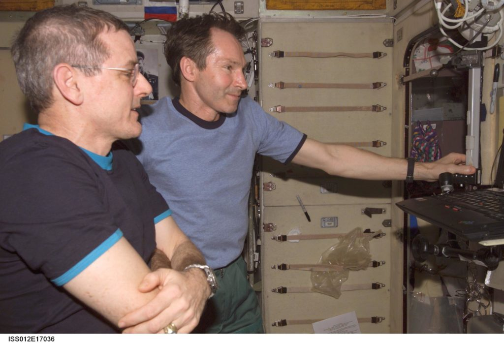 Tokarev and McArthur watch the RadioSkaf CD on a PC after opening the SM-RadioSkaf-11.1 Kit on Expedition 12