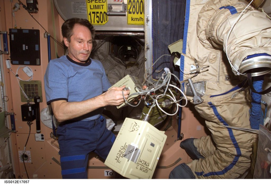 Tokarev puts battery boxes inside the Orlan suit as he assembles the RadioSkaf microsatellite on Expedition 12