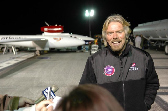 KENNEDY SPACE CENTER, FLA. -    During fueling of the Virgin Atlantic GlobalFlyer before dawn on NASA Kennedy Space Center's Shuttle Landing Facility (SLF), Sir Richard Branson talks to the media.  Branson is chairman and founder of Virgin Atlantic. The GlobalFlyer is in the background. Steve Fossett will pilot the GlobalFlyer on a record-breaking attempt by flying solo, non-stop without refueling, to surpass the current record for the longest flight of any aircraft.  Fossett is expected to take off from the KSC SLF.  Later, takeoff of the GlobalFlyer was postponed due to a fuel leak that appeared during the last moments of loading. The next planned takeoff attempt is 7 a.m. Feb. 8 from the SLF.   Photo credit: NASA/Kim Shiflett KSC-06pd0211