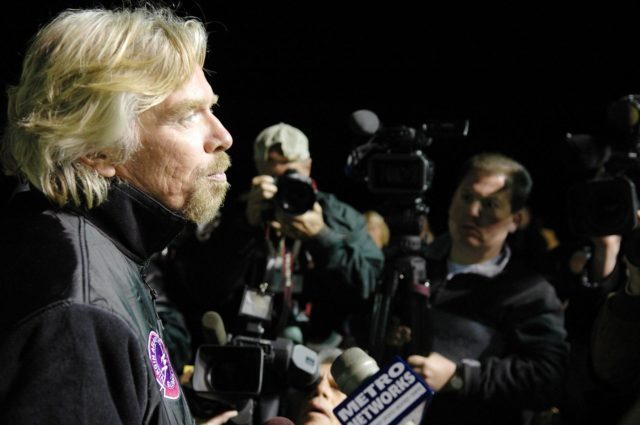 KENNEDY SPACE CENTER, FLA. -    Before dawn on NASA Kennedy Space Center's Shuttle Landing Facility (SLF), Sir Richard Branson talks to the media.  Branson is chairman and founder of Virgin Atlantic, which is sponsoring the GlobalFlyer. Steve Fossett will pilot the GlobalFlyer on a record-breaking attempt by flying solo, non-stop without refueling, to surpass the current record for the longest flight of any aircraft.  Fossett is expected to take off from the KSC SLF.  Later, takeoff of the GlobalFlyer was postponed due to a fuel leak that appeared during the last moments of loading. The next planned takeoff attempt is 7 a.m. Feb. 8 from the SLF.   Photo credit: NASA/Kim Shiflett KSC-06pd0212