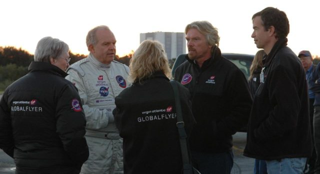 KENNEDY SPACE CENTER, FLA. -   Pilot Steve Fossett (facing camera, left) and Sir Richard Branson (second from right) talk with Virgin Atlantic GlobalFlyer team members about the fuel leak detected in the aircraft.   Branson is chairman and founder of Virgin Atlantic. Steve Fossett will pilot the GlobalFlyer on a record-breaking attempt by flying solo, non-stop without refueling, to surpass the current record for the longest flight of any aircraft.  Fossett was expected to take off from the KSC SLF before the takeoff was postponed due to the fuel leak that appeared in the last moments of loading. The next planned takeoff attempt is 7 a.m. Feb. 8 from the SLF.   Photo credit: NASA/Kim Shiflett KSC-06pd0217
