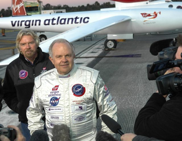 KENNEDY SPACE CENTER, FLA. -   Pilot Steve Fossett talks to the media about the reason the takeoff of the Virgin Atlantic GlobalFlyer was postponed.  Behind Fossett is Sir Richard Branson, chairman and founder of Virgin Atlantic.  Behind both is the GlobalFlyer aircraft.  Fossett will pilot the GlobalFlyer on a record-breaking attempt by flying solo, non-stop without refueling, to surpass the current record for the longest flight of any aircraft.  Fossett was expected to take off from the KSC SLF before the takeoff was postponed due to the fuel leak that appeared in the last moments of loading. The next planned takeoff attempt is 7 a.m. Feb. 8 from the SLF.   Photo credit: NASA/Kim Shiflett KSC-06pd0219