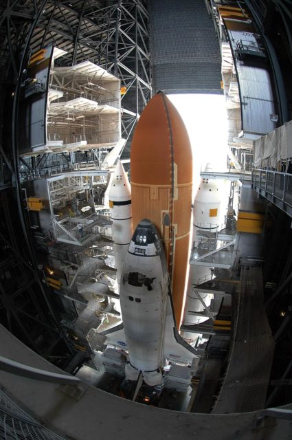 KENNEDY SPACE CENTER, FLA. --  A fish-eye view from inside NASA's Vehicle Assembly Building shows Space Shuttle Discovery as it begins its slow 4.2-mile journey via the crawlerway to Launch Pad 39B.  The shuttle rests on a mobile launcher platform that sits atop a crawler-transporter. First motion was at 12:45 p.m. EDT.  The rollout is an important step before launch of Discovery on mission STS-121 to the International Space Station. Discovery's launch is targeted for July 1 in a launch window that extends to July 19. During the 12-day mission, Discovery's crew will test new hardware and techniques to improve shuttle safety, as well as deliver supplies and make repairs to the station.  Photo credit: NASA/Kim Shiflett KSC-06pd0861