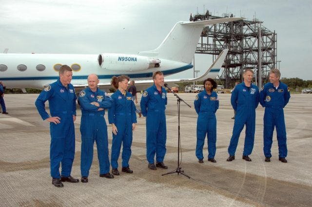 KENNEDY SPACE CENTER, FLA. - After landing at NASA's Kennedy Space Center aboard a Grumman G2 aircraft, the STS-121 crew gathers at a microphone for the media.  Mission Commander Steven Lindsey is introducing the crew, from left: Mission Specialist Michael Fossum, Pilot Mark Kelly, Mission Specialist Lisa Nowak, Lindsey, Mission Specialists Stephanie Wilson, Piers Sellers and Thomas Reiter, who represents the European Space Agency.  The crew is at the space center to take part in a Terminal Countdown Demonstration Test, or TCDT. Over several days, the crew will practice emergency egress from the pad and suit up in their orange flight suits for the simulated countdown to launch. Space Shuttle Discovery is designated to launch July 1 on mission STS-121.  It will carry supplies to the International Space Station.  Photo credit: NASA/Kim Shiflett KSC-06pd1039