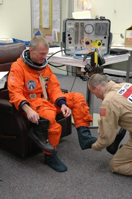 KENNEDY SPACE CENTER, FLA. -    STS-115 Commander Brent Jett is helped donning his launch suit before flying the Shuttle Training Aircraft to practice landing the shuttle.  STA practice is part of launch preparations.   The STA is a Grumman American Aviation-built Gulf Stream II jet that was modified to simulate an orbiter's cockpit, motion and visual cues, and handling qualities. In flight, the STA duplicates the orbiter's atmospheric descent trajectory from approximately 35,000 feet altitude to landing on a runway. Because the orbiter is unpowered during re-entry and landing, its high-speed glide must be perfectly executed the first time.  Mission STS-115 is scheduled to lift off about 4:30 p.m. Aug. 27.  The crew will deliver and install the P3/P4 segment to the port side of the integrated truss system on the International Space Station.  The truss includes a new set of photovoltaic solar arrays.  When unfurled to their full length of 240 feet, the arrays will provide additional power for the station in preparation for the delivery of international science modules over the next two years.  The mission is expected to last 11 days and includes three scheduled spacewalks.   Photo credit: NASA/Kim Shiflett KSC-06pd1905