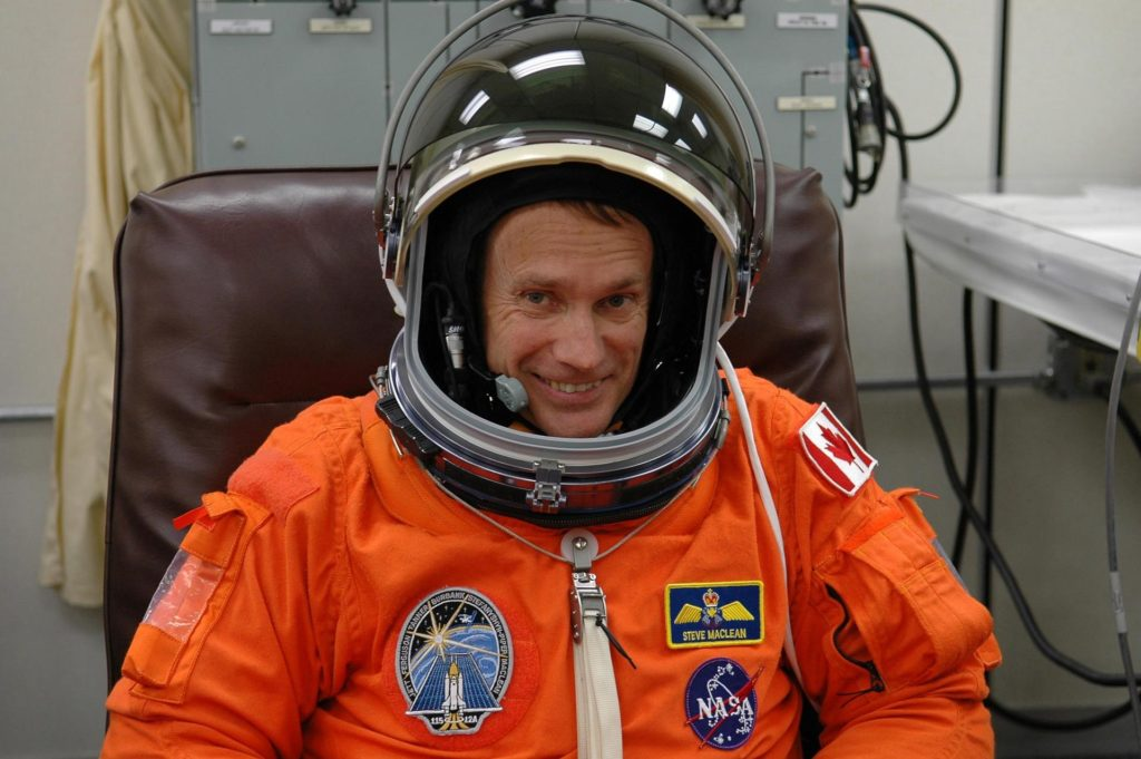 KENNEDY SPACE CENTER, FLA. -  In the Operations and Checkout Building at NASA Kennedy Space Center, STS-115 Mission Specialist Steven MacLean dons his helmet to complete suiting up for another attempt at liftoff.  MacLean is with the Canadian Space Agency.  The launch attempt on Sept. 8 was scrubbed due to an issue with a fuel cut-off sensor system inside the external fuel tank. This is one of several systems that protect the shuttle's main engines by triggering their shutdown if fuel runs unexpectedly low.  During the STS-115 mission, Atlantis' astronauts will deliver and install the 17.5-ton, bus-sized P3/P4 integrated truss segment on the station. The girder-like truss includes a set of giant solar arrays, batteries and associated electronics and will provide one-fourth of the total power-generation capability for the completed station. This mission is the 116th space shuttle flight, the 27th flight for orbiter Atlantis, and the 19th U.S. flight to the ISS. STS-115 is scheduled to last 11 days with a planned landing at KSC.  Photo credit: NASA/Kim Shiflett KSC-06pd2095