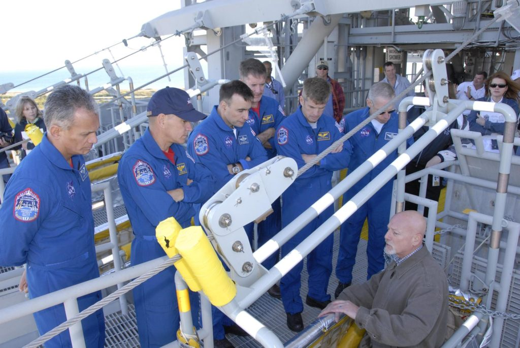 KENNEDY SPACE CENTER, FLA. --  At the 195-foot level of the fixed service structure on Launch Pad 39A, STS-117 crew members receive instruction on emergency egress during Terminal Countdown Demonstration Test activities. From left are Mission Specialist Danny Olivas, Commander Rick Sturckow, Pilot Lee Archambault, and Mission Specialists James Reilly, Steven Swanson and Patrick Forrester. They are practicing the emergency egress procedure using the slidewire basket system to get off the pad. The TCDT also includes M-113 armored personnel carrier training, and a simulated launch countdown. The mission payload aboard Space Shuttle Atlantis is the S3/S4 integrated truss structure, along with a third set of solar arrays and batteries. The crew of six astronauts will install the truss to continue assembly of the International Space Station. Photo credit: NASA/Kim Shiflett KSC-07pd0489