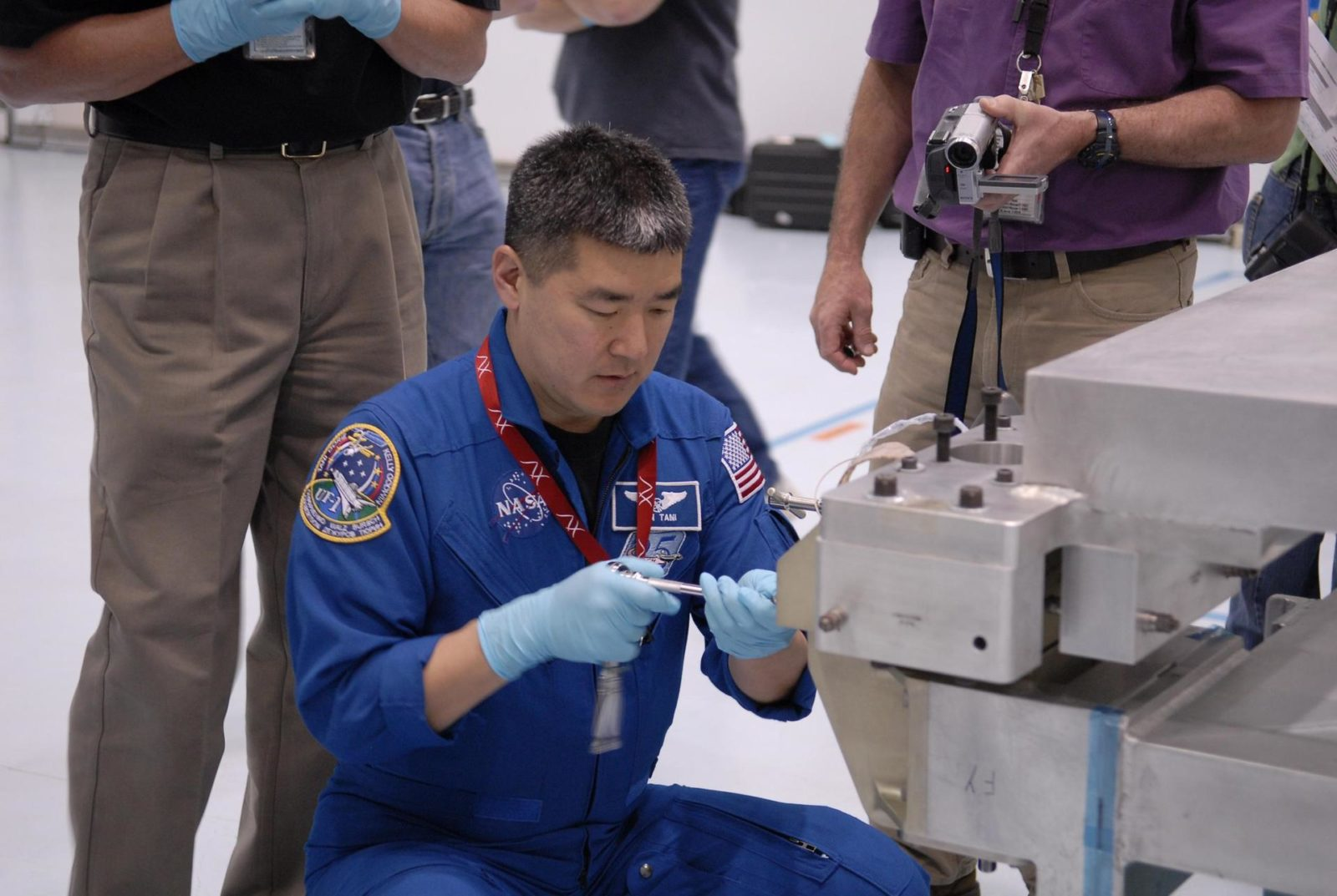 """KENNEDY SPACE CENTER, FLA. --  Mission STS-120 Mission Specialist Daniel Tani familiarizes himself with  equipment inside the Space Station Processing Facility during a visit to Kennedy Space Center. Other STS-120 crew members include Commander Pam Melroy, Pilot George Zamka, and Mission Specialists Scott Parazynski, Douglas Wheelock, Stephanie Wilson, Paolo Nespoli (with the European Space Agency) and Clayton Anderson.  Mission STS-120 will deliver the Node 2 """"Harmony"""" connecting module to the station. During the mission, Tani and Anderson will transfer to the station and remain as flight engineers for Expedition 15. The mission is tentatively scheduled for August of this year. Photo credit: NASA/Kim Shiflett KSC-07pd0742"""