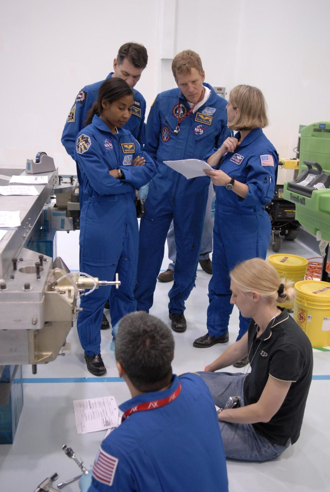 "KENNEDY SPACE CENTER, FLA. --  Mission STS-120 crew members familiarize themselves with equipment inside the Space Station Processing Facility during a visit to Kennedy Space Center. Standing from left, are Mission Specialists Stephanie Wilson, Paolo Nespoli (with the European Space Agency), Scott Parazynski and Commander Pam Melroy. In the foreground at left is Mission Specialist Daniel Tani.  Other crew members include Pilot George Zamka and Mission Specialists Douglas Wheelock and Clayton Anderson.  Mission STS-120 will deliver the Node 2 ""Harmony"" connecting module to the station.  During the mission, Tani and Anderson will transfer to the station and remain as flight engineers for Expedition 15. The mission is tentatively scheduled for August of this year. Photo credit: NASA/Kim Shiflett KSC-07pd0745"
