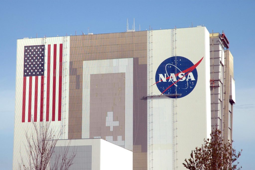 """KENNEDY SPACE CENTER, FLA.  --  The American flag and the NASA logo shine in the morning sun on the side of the Vehicle Assembly Building after completion of their repainting.  The flag spans an area 209 feet by 110 feet, or about 23, 437 square feet. Each stripe is 9 feet wide and each star is 6 feet in diameter. The NASA logo, which is known as the """"meatball,"""" measures 110 feet by 132 feet, or about 12,300 square feet.  The flag and logo were last painted in 1998, honoring NASA's 40th anniversary.  Photo credit: NASA/Jim Grossmann KSC-07pd0766"""