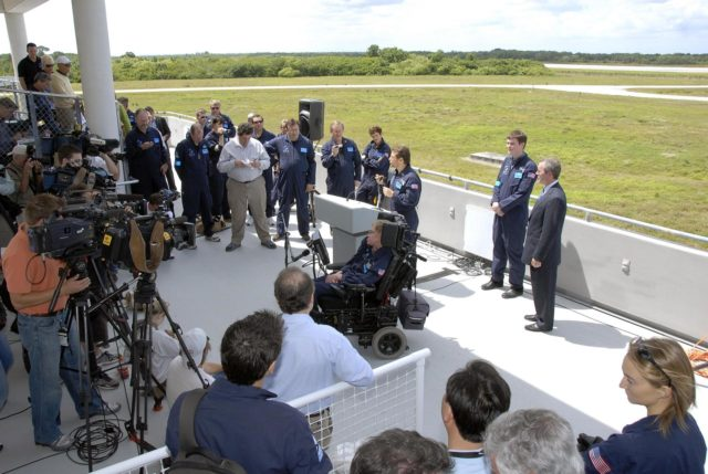 KENNEDY SPACE CENTER, FLA. -- At the Kennedy Space Center Shuttle Landing Facility, Peter Diamandis, founder of the Zero Gravity Corp., talks to the media about physicist Stephen Hawking's (in the wheelchair) first zero-gravity flight. The flight will be aboard a modified Boeing 727 aircraft owned by Zero Gravity Corp., a commercial company licensed to provide the public with weightless flight experiences.  Hawking developed amyotrophic lateral sclerosis disease in the 1960s, a type of motor neuron disease which would cost him the loss of almost all neuromuscular control. At the celebration of his 65th birthday on January 8 this year, Hawking announced his plans for a zero-gravity flight to prepare for a sub-orbital space flight in 2009 on Virgin Galactic's space service.  Photo credit: NASA/Kim Shiflett KSC-07pd0951