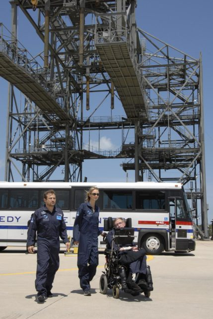 KENNEDY SPACE CENTER, FLA. -- At the Kennedy Space Center Shuttle Landing Facility, noted physicist Stephen Hawking, in the wheelchair, arrives at the runway for his first zero-gravity flight. The flight will be aboard a modified Boeing 727 aircraft owned by Zero Gravity Corp., a commercial company licensed to provide the public with weightless flight experiences.  At left is Peter Diamandis, founder of the Zero Gravity Corp. At center is Nicola O'Brien, a nurse practitioner who is Hawking's aide.  Hawking developed amyotrophic lateral sclerosis disease in the 1960s, a type of motor neuron disease which would cost him the loss of almost all neuromuscular control. At the celebration of his 65th birthday on January 8 this year, Hawking announced his plans for a zero-gravity flight to prepare for a sub-orbital space flight in 2009 on Virgin Galactic's space service.  Photo credit: NASA/Kim Shiflett KSC-07pd0953