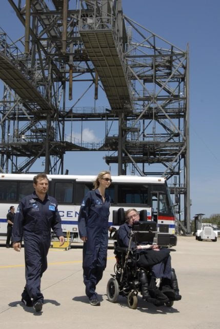 KENNEDY SPACE CENTER, FLA. -- At the Kennedy Space Center Shuttle Landing Facility, noted physicist Stephen Hawking, in the wheelchair, arrives at the runway for his first zero-gravity flight. The flight will be aboard a modified Boeing 727 aircraft owned by Zero Gravity Corp., a commercial company licensed to provide the public with weightless flight experiences.  At left is Peter Diamandis, founder of the Zero Gravity Corp. At center is Nicola O'Brien, a nurse practitioner who is Hawking's aide.  Hawking developed amyotrophic lateral sclerosis disease in the 1960s, a type of motor neuron disease which would cost him the loss of almost all neuromuscular control. At the celebration of his 65th birthday on January 8 this year, Hawking announced his plans for a zero-gravity flight to prepare for a sub-orbital space flight in 2009 on Virgin Galactic's space service.  Photo credit: NASA/Kim Shiflett KSC-07pd0954