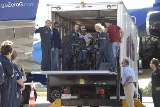 KENNEDY SPACE CENTER, FLA. -- Noted physicist Stephen Hawking (center) returns to the Kennedy Space Center Shuttle Landing Facility after a zero gravity flight.  At his side is Nicola O'Brien, a nurse practitioner who is Hawking's aide.  At far left on the truck's tail gate is Peter Diamandis, founder of the Zero Gravity Corp. that provided the flight aboard its modified Boeing 727.  Hawking suffers from amyotrophic lateral sclerosis (also known as Lou Gehrig's disease).  At the celebration of his 65th birthday on January 8 this year, Hawking announced his plans for a zero-gravity flight to prepare for a sub-orbital space flight in 2009 on Virgin Galactic's space service.  Photo credit: NASA/Kim Shiflett KSC-07pd0960