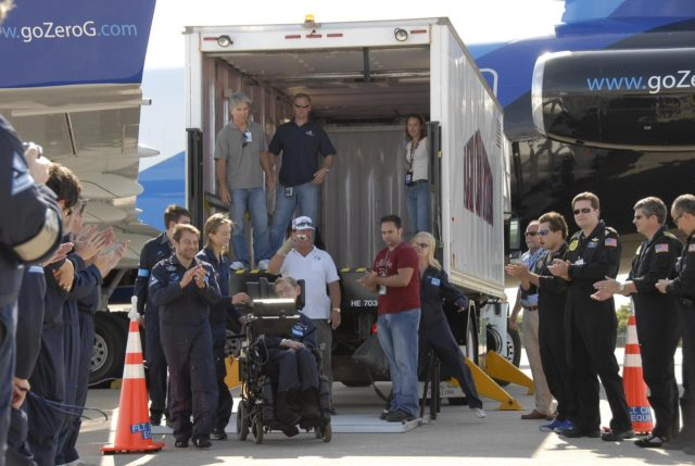 KENNEDY SPACE CENTER, FLA. --  Well-wishers greet noted physicist Stephen Hawking (in the wheelchair) at the Kennedy Space Center Shuttle Landing Facility after a zero gravity flight.  Next to him at left are Peter Diamandis, founder of the Zero Gravity Corp. that provided the flight aboard its modified Boeing 727, and Nicola O'Brien, a nurse practitioner who is Hawking's aide. Hawking suffers from amyotrophic lateral sclerosis (also known as Lou Gehrig's disease). At the celebration of his 65th birthday on January 8 this year, Hawking announced his plans for a zero-gravity flight to prepare for a sub-orbital space flight in 2009 on Virgin Galactic's space service.  Photo credit: NASA/Kim Shiflett KSC-07pd0962