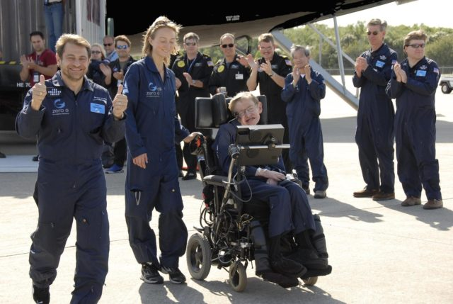 KENNEDY SPACE CENTER, FLA. -- Well-wishers greet noted physicist Stephen Hawking (in the wheelchair) at the Kennedy Space Center Shuttle Landing Facility after a zero gravity flight.  Next to him at left are Peter Diamandis, founder of the Zero Gravity Corp. that provided the flight aboard its modified Boeing 727, and Nicola O'Brien, a nurse practitioner who is Hawking's aide. Hawking suffers from amyotrophic lateral sclerosis (also known as Lou Gehrig's disease).  At the celebration of his 65th birthday on January 8 this year, Hawking announced his plans for a zero-gravity flight to prepare for a sub-orbital space flight in 2009 on Virgin Galactic's space service.  Photo credit: NASA/Kim Shiflett KSC-07pd0963