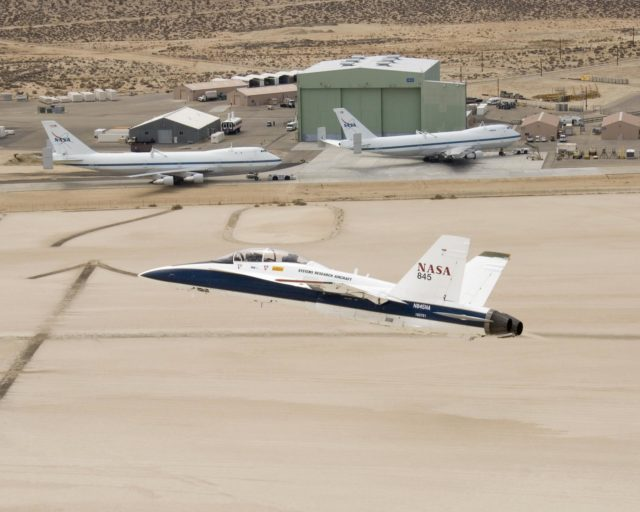 NASA's two Boeing 747 Shuttle Carrier Aircraft form the backdrop as pilot Dick Ewers banks NASA F/A-18 #845 low over Rogers Dry Lake to end a research flight. ED07-0090-06