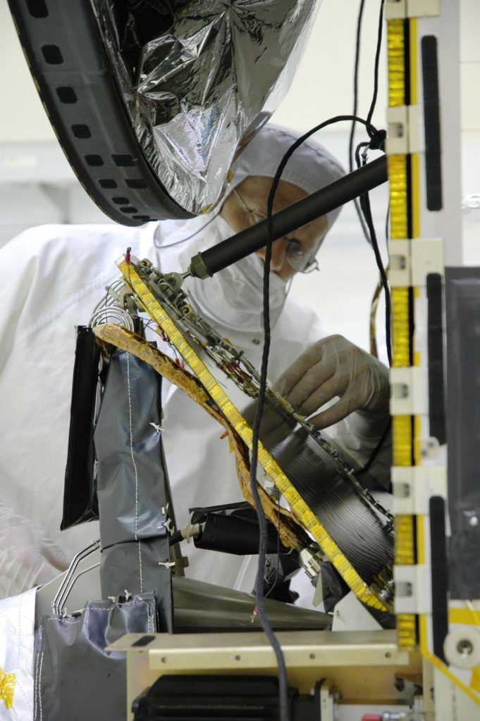 KENNEDY SPACE CENTER, FLA. -- In the Astrotech Space Operations facility, Orbital Science technicians install a computer chip on the Dawn spacecraft. The silicon chip holds the names of more than 360,000 space enthusiasts worldwide who signed up to participate in a virtual voyage to the asteroid belt and is about the size of an American five-cent coin. Dawn's mission is to explore two of the asteroid belt's most intriguing and dissimilar occupants: asteroid Vesta and the dwarf planet Ceres. Dawn is scheduled to launch June 30 from Launch Complex 17-B.  Photo credit: NASA/Jim Grossmann KSC-07pd1239