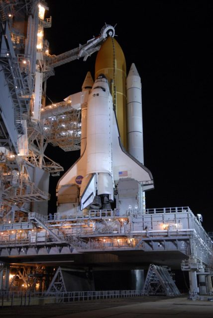 KENNEDY SPACE CENTER, FLA. --  After rollback of the rotating service structure, or RSS, on Launch Pad 39A, Space Shuttle Atlantis stands bathed in lights. Rollback is one of the milestones in preparation for the launch of mission STS-117 on June 8. Rollback started at 10:56 p.m. and was complete at 11:34 p.m EDT. The RSS provides protected access to the orbiter for changeout and servicing of payloads at the pad. The structure is supported by a rotating bridge that pivots about a vertical axis on the side of the pad's flame trench. The hinge column rests on the pad surface and is braced to the fixed service structure.  Support for the outer end of the bridge is provided by two eight-wheel, motor-driven trucks that move along circular twin rails installed flush with the pad surface. The track crosses the flame trench on a permanent bridge. The RSS is 102 feet long, 50 feet wide and 130 feet high. The structure has orbiter access platforms at five levels to provide access to the payload bay while the orbiter is being serviced in the RSS. Each platform has independent extendable planks that can be arranged to conform to a payload's configuration. This mission is the 118th shuttle flight and the 21st U.S. flight to the International Space Station and will deliver and install the S3/S4 truss segment, deploy a set of solar arrays and prepare them for operation.  Photo credit: NASA/Kim Shiflett KSC-07pd1392