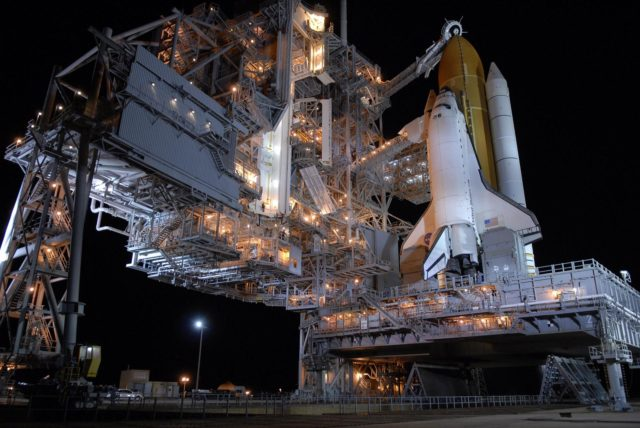 KENNEDY SPACE CENTER, FLA. --  Following rollback of the rotating service structure, or RSS, on Launch Pad 39A, Space Shuttle Atlantis stands bathed in lights atop a mobile launch platform. Rollback is one of the milestones in preparation for the launch of mission STS-117 on June 8. Rollback started at 10:56 p.m. and was complete at 11:34 p.m EDT. The RSS, the massive structure to the left of the shuttle, provides protected access to the orbiter for changeout and servicing of payloads at the pad. The structure is supported by a rotating bridge that pivots about a vertical axis on the side of the pad's flame trench. The hinge column rests on the pad surface and is braced to the fixed service structure.  Support for the outer end of the bridge is provided by two eight-wheel, motor-driven trucks that move along circular twin rails installed flush with the pad surface. The track crosses the flame trench on a permanent bridge. The RSS is 102 feet long, 50 feet wide and 130 feet high. The structure has orbiter access platforms at five levels to provide access to the payload bay while the orbiter is being serviced in the RSS. Each platform has independent extendable planks that can be arranged to conform to a payload's configuration. This mission is the 118th shuttle flight and the 21st U.S. flight to the International Space Station and will deliver and install the S3/S4 truss segment, deploy a set of solar arrays and prepare them for operation.  Photo credit: NASA/Kim Shiflett KSC-07pd1393