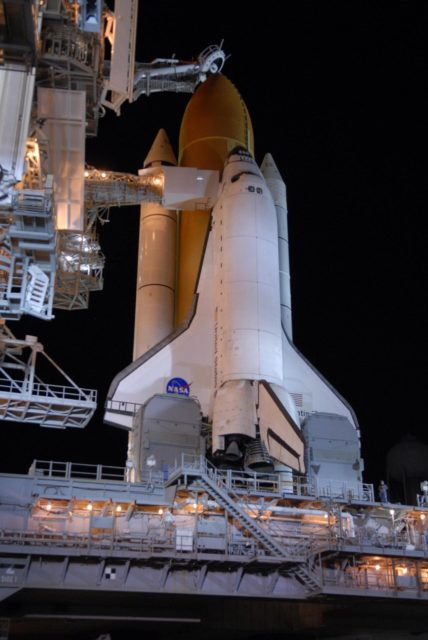 """KENNEDY SPACE CENTER, FLA. --  Following rollback of the rotating service structure, or RSS, on Launch Pad 39A, Space Shuttle Atlantis stands bathed in lights atop a mobile launch platform. Rollback is one of the milestones in preparation for the launch of mission STS-117 on June 8. Rollback started at 10:56 p.m. and was complete at 11:34 p.m EDT. The RSS provides protected access to the orbiter for changeout and servicing of payloads at the pad. Connecting the RSS to the cockpit of the shuttle is the orbiter access arm with the White Room extended. The White Room provides access into the orbiter for the astronauts. Above the external tank is the vent hood (known as the """"beanie cap"""") at the end of the gaseous oxygen vent arm. Vapors are created as the liquid oxygen in the external tank boil off. The hood vents the gaseous oxygen vapors away from the space shuttle vehicle. This mission is the 118th shuttle flight and the 21st U.S. flight to the International Space Station and will deliver and install the S3/S4 truss segment, deploy a set of solar arrays and prepare them for operation.  Photo credit: NASA/Kim Shiflett KSC-07pd1394"""
