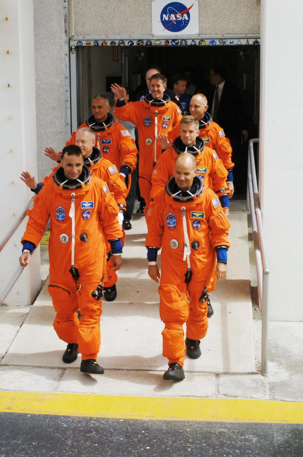 """STS117-S-006 (8 June 2007) --- After suiting up, the STS-117 crewmembers exit the Operations and Checkout Building to board the Astrovan, which will take them to launch pad 39A at Kennedy Space Center. On the right (front to back) are astronauts Rick Sturckow, commander; Steven Swanson, Clayton Anderson and Jim Reilly (center back), all mission specialists. On the left (front to back) are astronauts Lee Archambault, pilot; Patrick Forrester and John """"Danny"""" Olivas, both mission specialists. Anderson will join Expedition 15 in progress to serve as a flight engineer aboard the International Space Station. Atlantis will link up with the International Space Station on Sunday, June 10, to begin a joint mission that will increase the complex's power generation capability. Using the shuttle and station robotic arms and conducting three scheduled spacewalks, the astronauts will install another set of giant solar array wings on the station and retract another array, preparing it for a future move. STS117-S-006"""