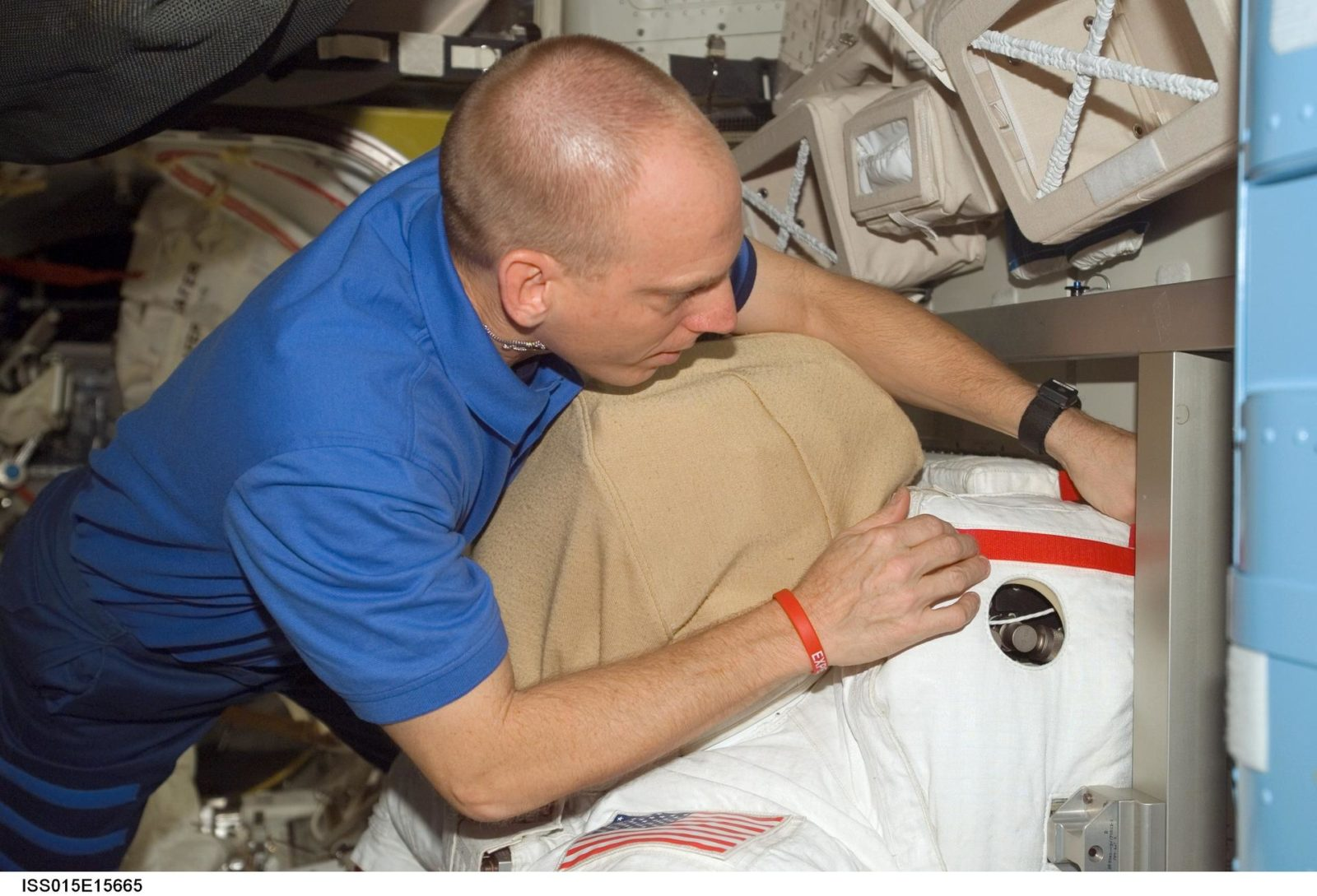View of Anderson working with an EMU in the A/L during Expedition 15